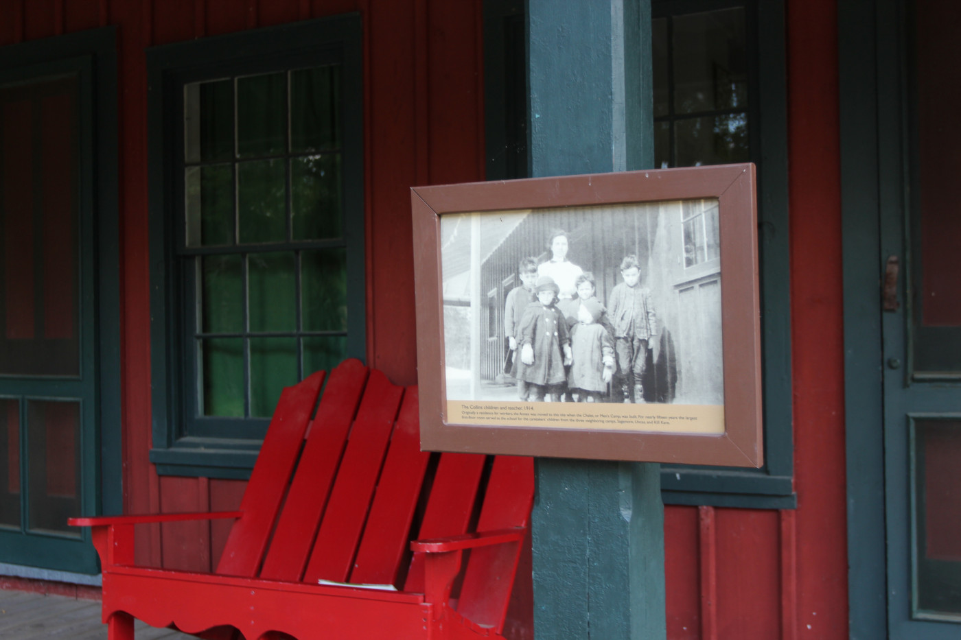 The porch of Sagamore's schoolhouse, with photo of children and their teacher at the school.